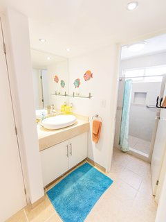 Second bedroom with vanity area and fully tiled shower and toilet.