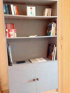 Bibliothèque dans l'entrée avec livres et dépliants sur Nice et sa région