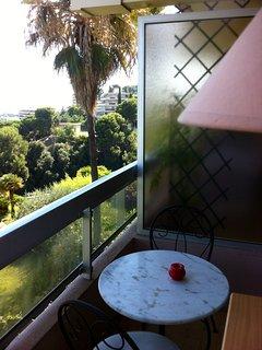 Table et chaises sur le balcon vue panoramique sur la mer et la verdure