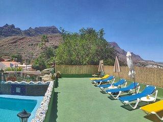 Solarium con hamacas, mesas, sombrillas al lado de la piscina privada
