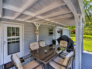 Relax on the covered deck at this charming Merritt vacation rental home.