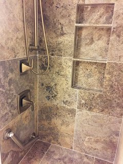 Travertine marble shower, Moen fixtures, and heated floor and shower bench