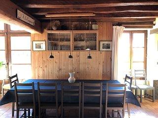 Espace salle à manger avec grande table pouvant accueillir 14 convives assis