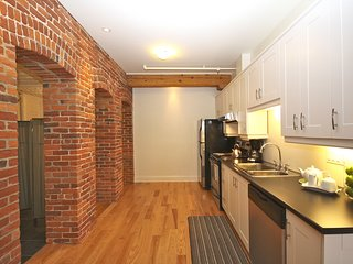 The fully-equipped kitchen accentuated by historic brick walls.