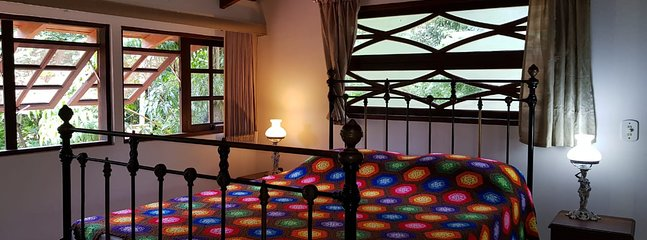 Suíte master, cama king size - piso superior com vista para a mata e jardim