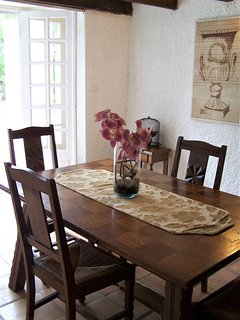 The dining setting seats four. French doors open onto the sunny terrace and garden