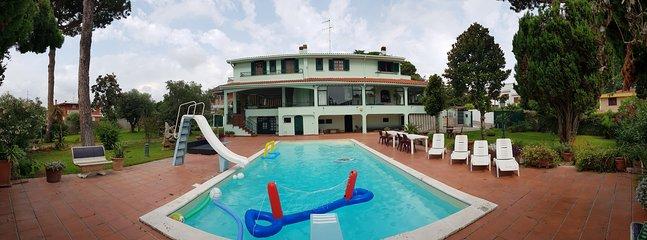 Panoramautsikt över villan, poolen och trädgården