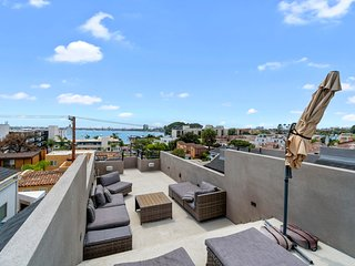 Modern home w/ a fireplace & enclosed yard plus bay views from the rooftop patio