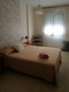 Segundo dormitorio equipado con ropa de cama y juego de toallas