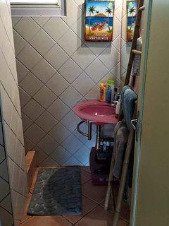 Salle de bain fonctionnelle avec douche, lavabo et wc.