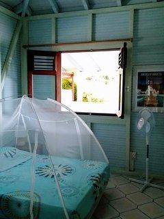Chambre bleue avec penderie, ventilateur, moustiquaire, et vue sur mer.