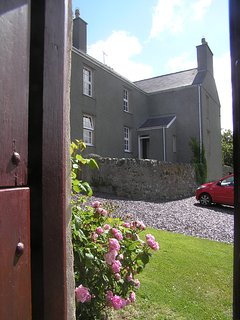 Back Wing entrance and patio, an enclosed lawned garden is to the rear