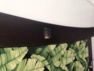 La tête de lit avec son tissu imprimé tropical et sa nacre incrustée