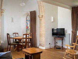 The beautiful open plan living space, with wooden floors and stained glass windows
