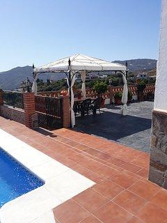Terraza y carpa al lado de la piscina