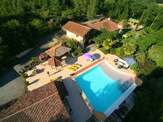 Two houses in a beautiful park with a large pool and views.