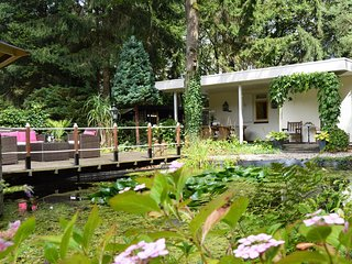 A detached bungalow with outdoor fireplace, covered terrace and pond in a forest
