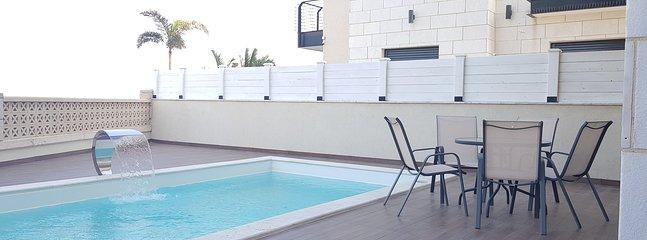 piscina espaciosa y privada con jacuzzi en cascada y luces de la piscina