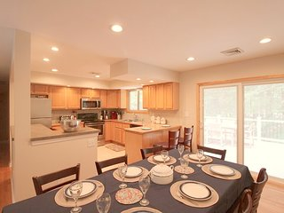 Kitchen and dining with sliding glass door to deck