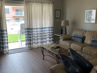 Bright and airy living room, patio and pool just steps away!
