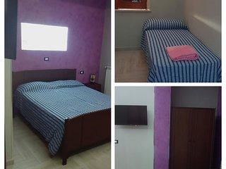 Camera da letto con un letto matrimoniale e un letto singolo con televisore LCD a parete