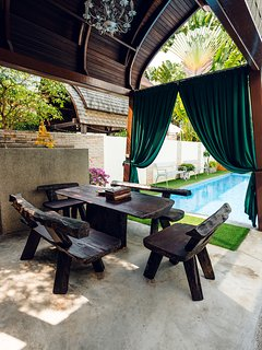 Patio with wooden table and chairs for confortable outdoor picknick near private swimming pool