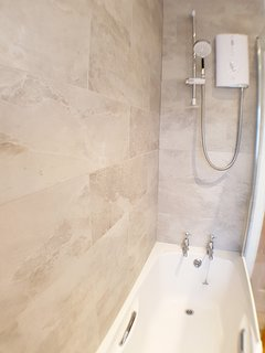 Shower over the bath, with safety glass shower screen