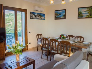 Living area, with the big table for 8 people , the sofa bed and the access to the big terrace