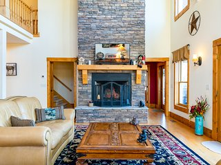 Great room with leather couches and two story rock fireplace