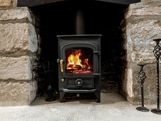 The beautiful living room contains a cosy wood burning stove