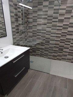 Baño con lavabo mueble baño espejo, plato ducha con mampara, inodoro, bidé e iluminación led