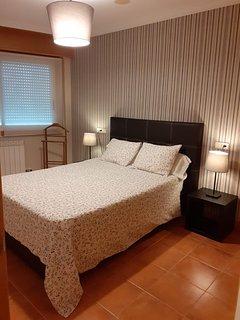 Dormitorio con cama matrimonial TV y amplio armario