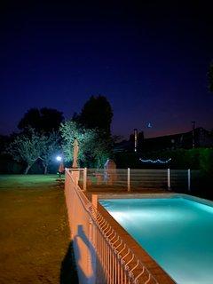 Vista nocturna piscina y jardín
