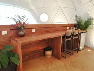 Wooden bar with high chairs, where you can drink coffee or use it as a desk.