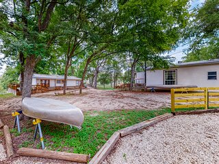 Colorful riverfront property w/ main house, bunkhouse, and trailer w/ amenities!