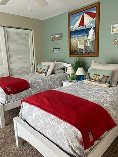 Guest bedroom with twin beds and roll away bed in closed with baby bed and high chair