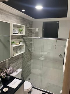 Banheiro  social : chuveiro  elétrico,  porta de Box, armários, secador e chapinha, ducha higiênica,