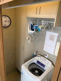 Área serviço: maq. de lavar, 2 varais, tanque pia, vaso sanitário, armários, mesa e ferro de passar