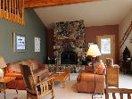 The living room has cushy leather sofas situated around the grand river rock fireplace.