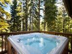 The private hot tub sits on the deck with a view of the forest.