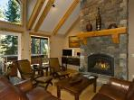 High beamed ceiling living room with granite gas fireplace.