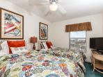This guest bedroom with twin size beds and a flat-screen TV make