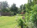 Sunny south facing flower filled courtyard garden, landscaped grounds & shady communal dining barn