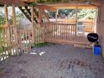 Lower deck with patio table, chairs, charcoal BBQ and small fenced yard.