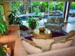 The living room leads into the lanai conversation area and the garden pool.
