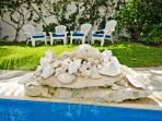 A small rock waterfall gently pours water into the upper level of the pool