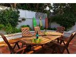 Large teak table and chairs on the spacious patio with plenty of privacy and space