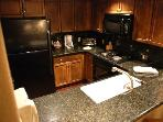 Granite counters in the fully-furnished kitchen