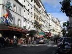 Rue des Abbesses, the vibrant quartier where you will play and shop with your neighbors.