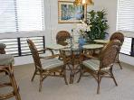 The dining area features both a counter with bar stools & an oval dining table.